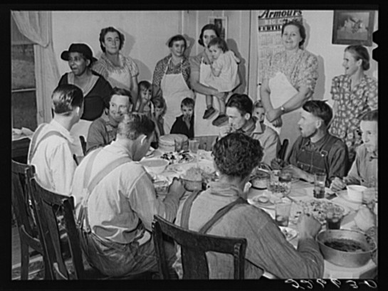 After the corn shucking, women and children of the Wilkins family gather around while the men eat.